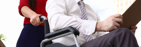 Close-up of woman co-worker accompany man in disabled carriage. Employee reading important papers. Business and adaptation of people with disabilities in society concept