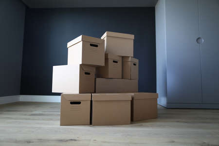 Empty cardboard boxes stand in an empty room. Empty office interior, boxes stand on floor. Loading property in boxes. Items are reliably protected from damage during loading and transportation Imagens