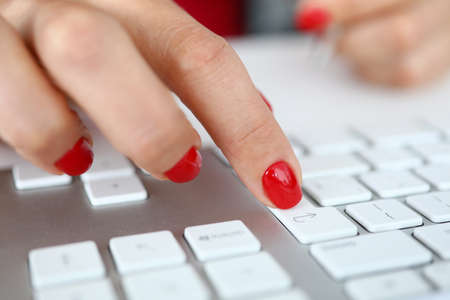 Close-up of woman pressing knob on white keyboard. Fresh stylish red manicure. Female employee working in personal office. Clerk in cabinet. Business and information concept Stok Fotoğraf