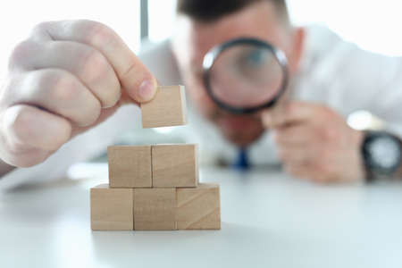 Close-up of man looking on wooden cubes stack through magnifying glass. Concentrated person building pyramid on working table. Business strategy and smart decision concept