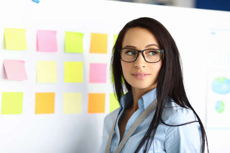 Portrait of charming young woman looking away posing on camera. Successful clerk wearing blue shirt and glasses. White board with notes. Business and career growth concept Stok Fotoğraf