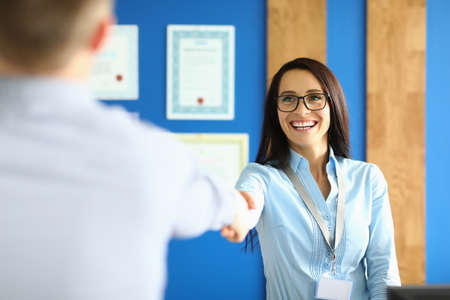 Portrait of business colleagues shaking hands and smiling. Pretty young woman in stylish blue shirt wearing glasses. Working moment in office. Meeting on conference room. Career concept Stok Fotoğraf