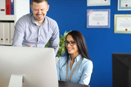 Portrait of smiling worker involved in process. Cheerful middle-aged man and pretty young woman using computer. Blue wall in modern office. Successful business and career concept Stok Fotoğraf - 151447675
