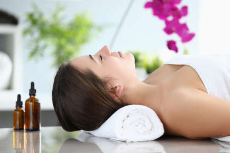 Close-up of young beautiful woman laying on massage table in spa salon. Relaxed lady smiling and feeling happy after hard day. Take care of yourself. Relaxation and beauty day concept