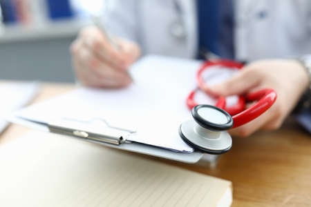 Close-up of man holding red tool stethoscope and sitting in luxury clinic office. Professional qualified medical worker writing in prescription. Person in white uniform. Modern medicine concept