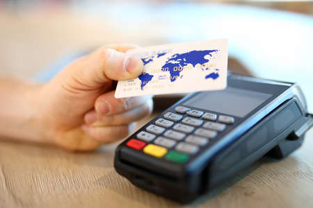 Close-up of terminal and person with white plastic credit card. Cashier machine to withdrawals money. Nfc technology. Finance and cashless way to pay for purchase. Contactless payment concept