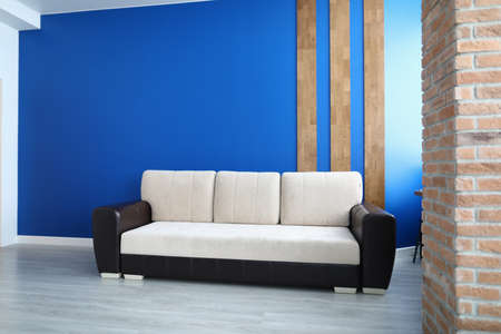 Close-up of comfy sofa for office or living room. Stylish white colour and black insert. Bright blue wall with wooden lines decoration. Laminate on floor. Comfort and trendy interior design concept