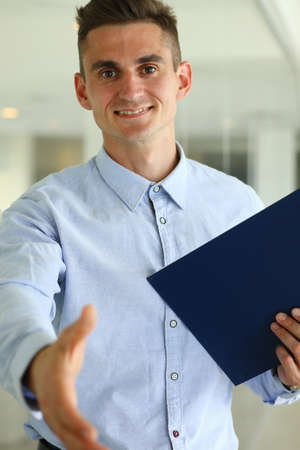 Waist up portrait of smiling male in shirt standing and holding folder while giving hand for greeting
