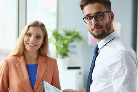 Portrait of smiling bearded male with tie and jolly female as they are standing and discussing financial chart