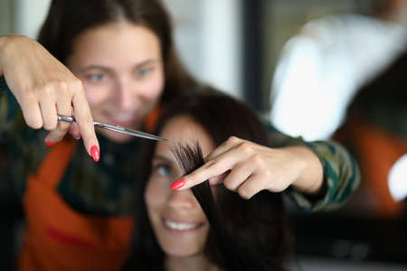Beautiful woman in apron hold scissors in her hand and cut client hair close-up. Two women smile. Hairdresser show woman what length of hair to trim.
