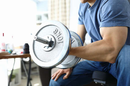 Large male hand with biceps hold ten kilogram metal dumbbell. Man sit on simulator and pumps muscles with heavy weights. Keeping fit in gym. Male biceps close up.