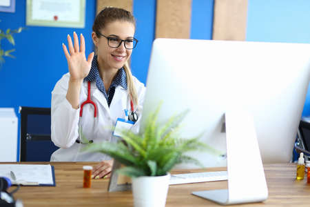 A young specialist sits in front of a computer monitor and greets the patient online. Primary diagnosis of patient health using telemedicine