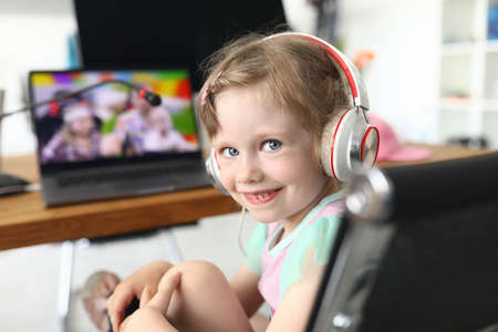 Little girl sits smiling on a chair in front of a laptop. Child watching a video about the trip with his family Foto de archivo
