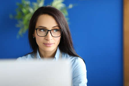 A young woman with glasses sits in the office in front of the monitor. Beautiful female worker with glasses is distracted from work