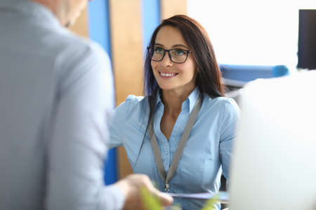 The woman in the office looks at the man with admiration. An intern with a badge learns to achieve certain goals through an internship