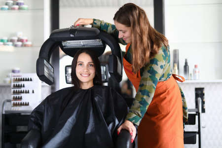 Happy hairdresser sets up equipment for drying hair. A completed haircut emphasizes strengths and hides flaws