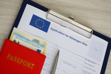 On the table is an application for a Schengen visa. Submission of documents and payment of visa fee Foto de archivo