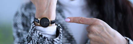 Displeased woman shows time on her wristwatch. Woman analyzes market in global and local senses, calculating possible risks. Process implementing decisions and monitoring their implementation