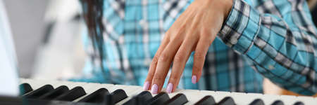 Close-up of female hands learning to play on modern synthesizer. Musician playing piano with notes. Talented composer creating melody. Music and art concept Stock Photo