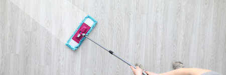Male hant hold plastic mop and wash dirty ploor closeup background. Professional cleaning concept