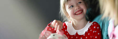Happy little girl in red dress hold silver coin in hand. Home finance budget concept