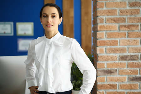 Beautiful woman in a white blouse is standing in the office against the background of a brick wall. Specialist woman in her office Foto de archivo