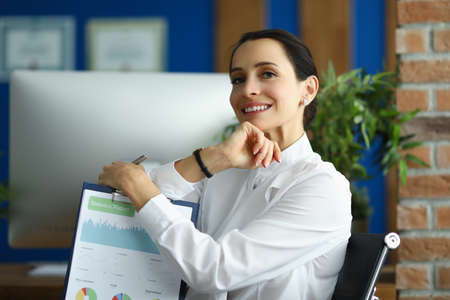 A smiling woman is sitting at the workplace with a statistical report in her hands. The employee carefully performs the work
