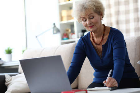 An elderly woman sits with a laptop and makes notes in a notebook. Computer literacy training for seniors