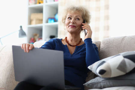 An elderly woman holds a laptop and calls on the phone. Grandma enjoys site support