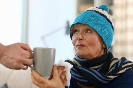 An elderly lady in a knitted hat sits on a sofa and holds a cup. Weak immune system in old age. Cold medicine for mother Standard-Bild
