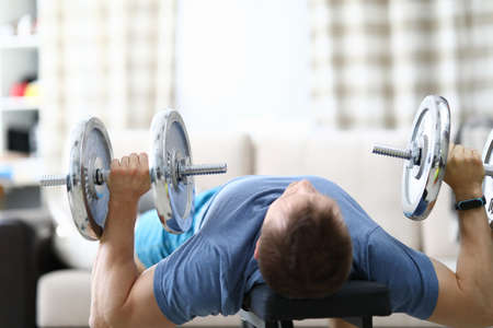 A man at home raises heavy dumbbells from a prone position. Interval and cardio training for burning fat