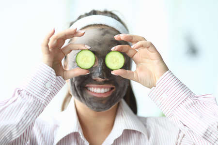 Woman in a shirt with a cosmetic mask on her face. Woman shows cucumbers over eyes and smiles 스톡 콘텐츠