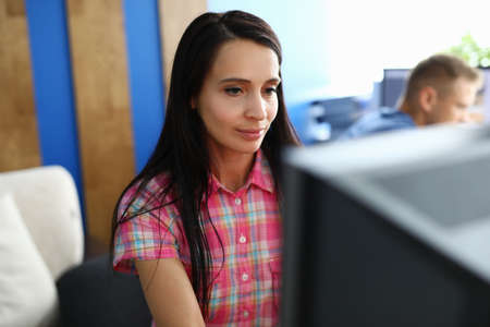 A young woman sits in an office at the monitor and works intently. Employees sit in the same room Stock Photo