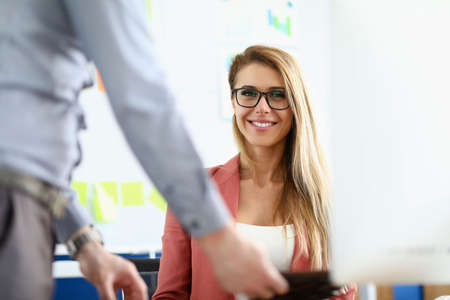 The woman sits in front of the monitor in the office and smiles. Male boss has a flexible approach to subordinates Imagens