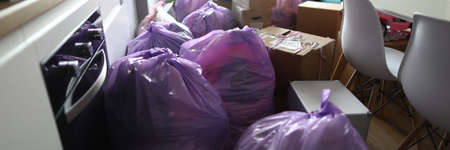 Kitchen is full garbage bags and cardboard boxes. Hings are packed in packages and boxes for moving to other housing. Old things collected for garbage disposal. General cleaning in kitchen