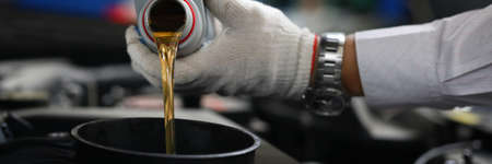 Close-up hands in gloves pour oil into car tank. Selection engine oil. Necessary volume of filling. Safety precautions. Troubleshooting, technology installation additional equipment. Stock fotó
