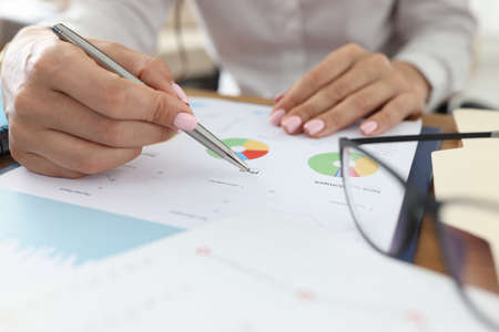 Female hand holds pen on graphs with indicators next to glasses. Small and medium business development concept Standard-Bild
