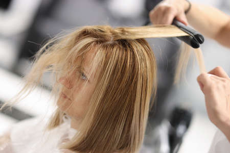 For woman, the master lifts roots of corrugated hair. Hair styling and hairstyles concept Foto de archivo