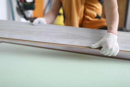 Gloved craftsman holds laminate board indoors. Floor coverings concept