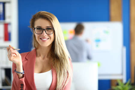 Blonde woman in a jacket with glasses stands in the office and smiles. Consulting clients in the bank concept