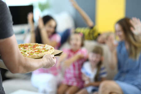 Man holds pizza in his hands against background of rejoicing children and adults. Pizza delivery conce
