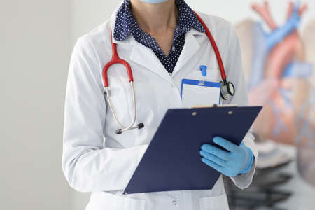 Doctor in white coat and gloves holds clipboard. Medical examination and diagnosis concept Stock Photo