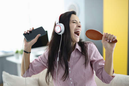 Woman with headphones and comb in her hands sings emotionally. Stress relief while singing concept
