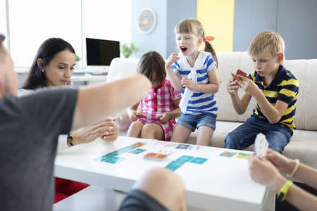 Adults and children are sitting at table and holding playing cards girl stood up and shouts. Child cannot play concept