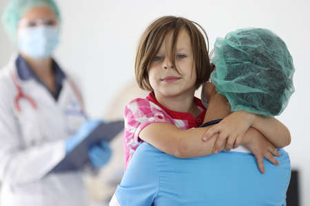 Doctor holds girl in his arms in medical office. Emergency medical care concept Standard-Bild