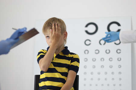 Boy at an ophthalmologists appointment closes one eye and answers questions. Visual examination in children concept Stock fotó