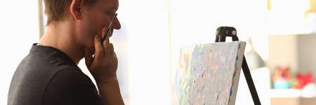 Portrait of talented young man creating masterpiece. Artist thinking on idea for painting and holding paintbrush. Work as hobby. Art and creativity concept Archivio Fotografico