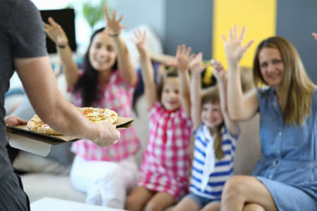 Man holds pizza in his hands on couch, he is happily greeted by girls with mothers. Organization of childrens parties concept
