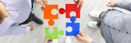Group businees people hold color element puzzle top view background closeup. Each fulfills its task division of labor concept Archivio Fotografico