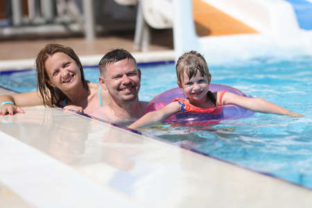 Woman, man and daughter smile together. Family swim in pool in sun. Stock fotó